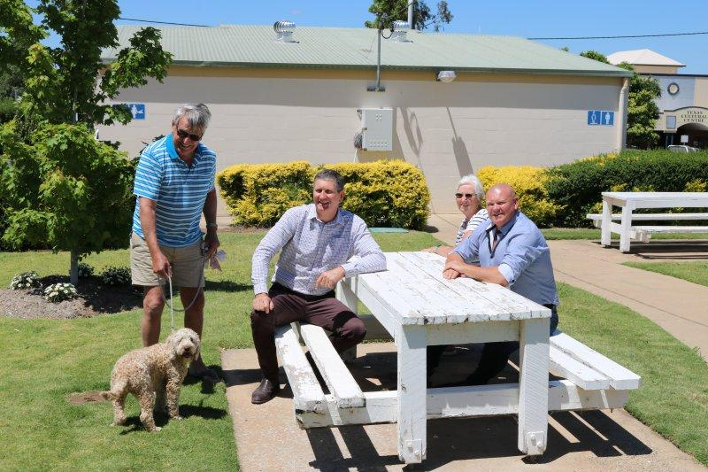 The Honourable Councillor Lawrence Springborg AM with some travellers and their dog at a picnic table in the park in Texas Qld