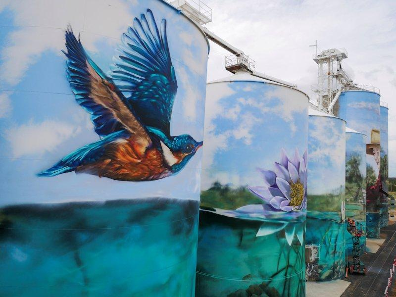 final stage of the yelarbon silo artwork completed featuring kingfisher flying over lagoon and water lily in the lagoon in shades of blue and green