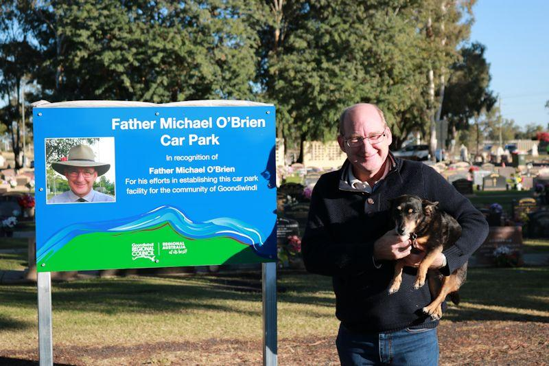 fr obrien holding his dog sister rosie standing next to the sign in the carpark named after him at the goondiwindi cemetery